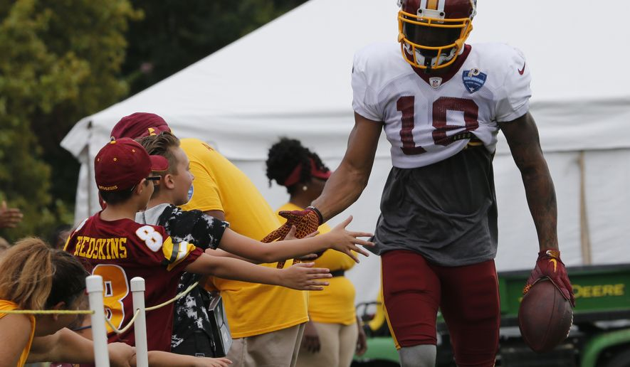 Washington Redskins wide receiver Josh Doctson slaps hands with fans during the morning session at NFL football training camp in Richmond, Va., Wednesday, Aug. 1, 2018. (AP Photo/Steve Helber)