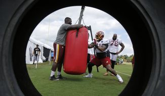 Washington Redskins offensive tackle Trent Williams (71) runs through a drill as teammate Morgan Moses (76) watches during the morning session of the Redskins NFL football training camp in Richmond, Va., Wednesday, Aug. 1, 2018. (AP Photo/Steve Helber) ** FILE **