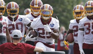 FILE - In this July 27, 2018, file photo, Washington Redskins running back Chris Thompson (25) runs a drill during the morning session of the Redskins NFL football training camp in Richmond, Va. More than eight months since breaking his right fibula, Redskins running back Chris Thompson is just now getting team snaps in training camp and still worries about the injury. Washington's offensive MVP last season is trying to overcome the mental hurdle of coming back from the serious injury that necessitated major surgery. (AP Photo/Steve Helber) ** FILE **
