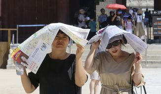 Women use papers to avoid sunshine at the Gyeongbok Palace, the main royal palace during the Joseon Dynasty, in Seoul, South Korea, Wednesday, Aug. 1, 2018. South Korean Meteorological Administration issued a heat wave warning for Seoul and other cities. (AP Photo/Ahn Young-joon)