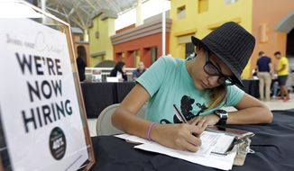 In this Oct. 3, 2017, file photo, job seeker Alejandra Bastidas fills out an application at a job fair at Dolphin Mall in Sweetwater, Fla. (AP Photo/Alan Diaz, File)