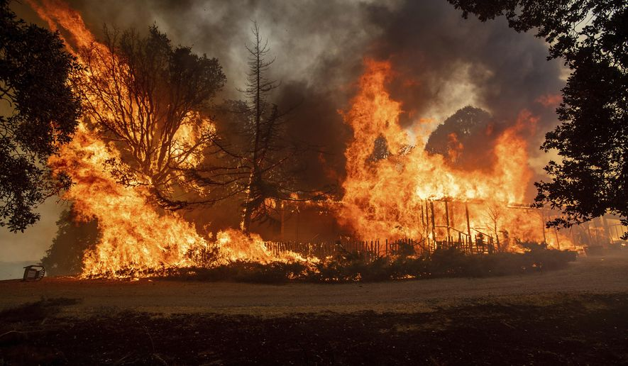 Flames consume a home as the River Fire tears through Lakeport, Calif., Tuesday, July 31, 2018. (AP Photo/Noah Berger)