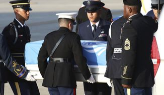 Honor guards carry the remains of U.S. servicemen killed in the Korean War and collected in North Korea, during a ceremony at the Osan Air Base in Pyeongtaek, South Korea, Wednesday, Aug. 1, 2018. North Korea handed over 55 boxes of the remains last week as part of agreements reached during a historic June summit between its leader Kim Jong Un and U.S. President Donald Trump. (Chung Sung-Jun/Pool Photo via AP)