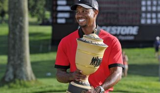 FILE - In this Aug. 4, 2013, file photo, Tiger Woods holds the trophy after winning the Bridgestone Invitational golf tournament at Firestone Country Club in Akron, Ohio. The biggest win for Tiger Woods this year was simply getting a chance to play. He narrowly qualified for the Bridgestone Invitational,  which is being held for the last time on the Firestone course where Woods has won eight times. (AP Photo/Phil Long, File)