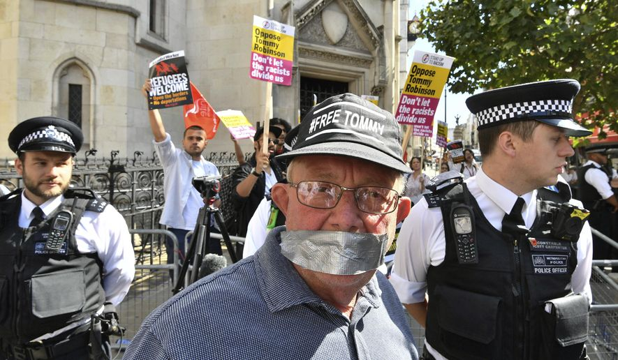 A supporter of Tommy Robinson in the foreground poses for a photo as Stand Up to Racism demonstrators protest outside the Royal Courts of Justice, in London, Wednesday, Aug. 1, 2018.  A British court has ordered prominent far-right activist Tommy Robinson to be released on bail while he appeals a finding of contempt of court. Robinson had been jailed for 13 months after live-streaming outside a criminal trial in violation of reporting restrictions. Court. (John Stillwell/PA via AP)