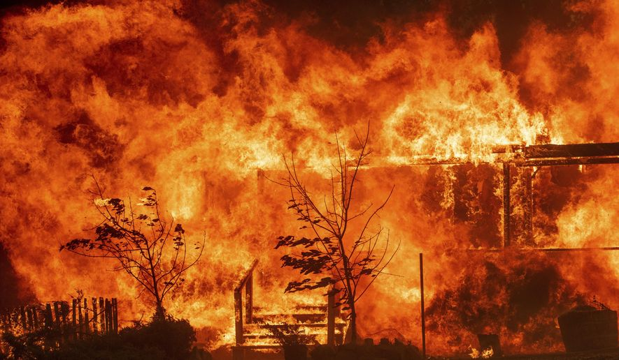 Flames consume a home as the River Fire tears though Lakeport, Calif., on Tuesday, July 31, 2018. (AP Photo/Noah Berger, File)