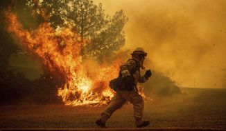 REMOVES NAME OF STREET AS STREET NAME IS UNKNOWN - A firefighter runs while trying to save a home as a wildfire tears through Lakeport, Calif., Tuesday, July 31, 2018. The residence eventually burned. Firefighters pressed their battle against a pair of fires across Mendocino and Lake counties. In all, roughly 19,000 people have been warned to flee and 10,000 homes remain under threat. (AP Photo/Noah Berger)