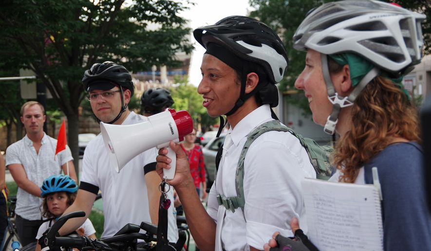 Cyrus Habib (center) speaks to a crowd of 50 cyclists on Tuesday before leading a memorial procession for his brother who was killed while riding his bike last month. Rachel Maisler (right), of the D.C. Bicycle Advisory Council, planned the ride. (Julia Airey/The Washington Times)