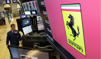 The logo for Ferrari is displayed above a trading post on the floor of the New York Stock Exchange, Wednesday, Aug. 1, 2018. Sports carmaker Ferrari confirms its 2018 earnings forecasts after posting an 18-percent rise in second-quarter profits and a rise in deliveries. (AP Photo/Richard Drew)