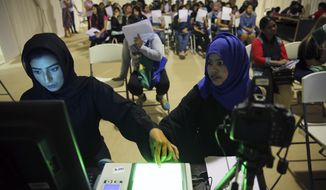 A government employee, left, takes the fingerprints of a foreign worker at a visa processing center in Al Aweer, about 30 kms, 18.6 miles, east of Dubai, United Arab Emirates, Wednesday, Aug. 1, 2018. The UAE has begun a three-month visa amnesty program hoping to resolve a Catch 22 situation for foreign workers who are fined daily for overstaying the time allowed, but cannot leave the Gulf nation until they have paid the penalties they owe. (AP Photo/Kamran Jebreili)