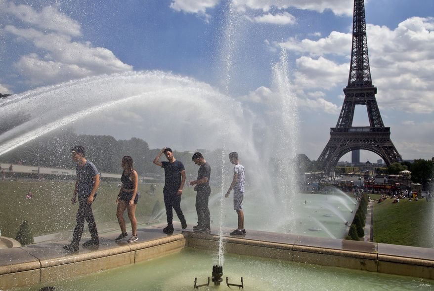 People cool off as they walk along the fountain of Warsaw near Eiffel Tower in Paris, France, Wednesday, Aug, 1, 2018. Temperatures in Paris are forecast to reach 3O degrees C (86 F) on Wednesday. (AP Photo/Michel Euler)