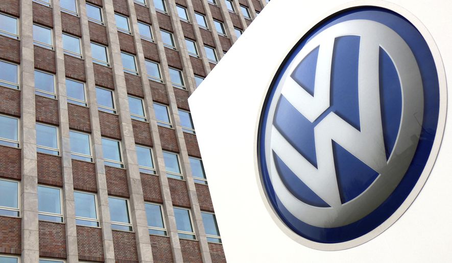 FILE - In this Friday, April 13, 2018 file photo,  Volkswagen logo is pictured in front of a company building in Wolfsburg, Germany. German carmaker Volkswagen reports second-quarter earnings on Wednesday Aug 1, 2018. (AP Photo/Michael Sohn, File)