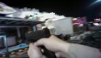 In this Sunday, Oct. 1, 2017, image taken from police body cam video released Wednesday, July 25, 2018, by the Las Vegas Metropolitan Police Department, an armed law enforcement official points his gun while searching for what authorities thought were multiple shooters inside and outside a Las Vegas Strip hotel, where a gunman firing from upper-floor windows killed 58 people and injured hundreds. (Las Vegas Metropolitan Police Department via AP)