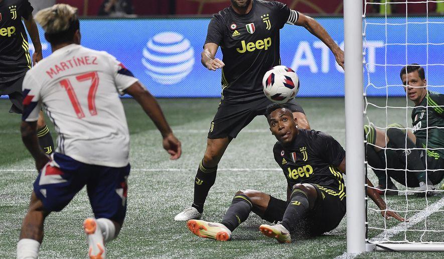 MLS All-Star forward Josef Martinez (17) goes for the ball against Juventus goalkeeper Wojciech Szczesny, right, during the MLS All-Star soccer match, Wednesday, Aug. 1, 2018, in Atlanta. (AP Photo/John Amis)