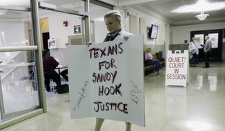 """Kelly Jones, ex-wife of """"Infowars"""" host Alex Jones, carries a sign as she arrives at the Travis County Courthouse, Wednesday, Aug. 1, 2018, in Austin, Texas. Alex Jones wants a Texas judge to dismiss a defamation lawsuit filed against him by families of some of the children killed in the 2012 mass shooting at Sandy Hook Elementary School. (AP Photo/Eric Gay)"""