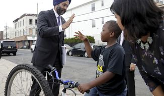 New Jersey Attorney General Gurbir Grewal, center, greets  Jasim Jackson, 9, after a news conference announcing pollution lawsuits filed by the state, Wednesday, Aug. 1, 2018, in Newark, N.J. Grewal said it's the largest single-day action the state has taken in at least a decade and the first new natural resources damages case since 2008.  Grewal didn't have an estimate for what the state might recover financially but said the cases could take a long time to prosecute. The cases include two sites in Newark, two in Woodbridge and one each in Atlantic City and Warren County. (AP Photo/Julio Cortez)