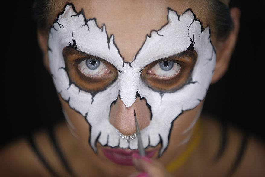 In this Friday, July 27, 2018 photo, Serbian make-up artist Mirjana Milosevic known professionally as 'Kika' paints her face in her studio at her home in the central Serbian town of Smederevo, Serbia. Milosevic has won international recognition for the skin illusions that she applies on her own body, later posting the whole process on her You Tube channel and social networks. (AP Photo/Darko Vojinovic)
