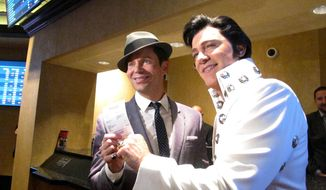 Frank Sinatra impersonator Brian Duprey, left, and Elvis Presley impersonator Kevin Mills, right, show off a ticket for a bet they placed on the New York Yankees moments after Harrah's casino in Atlantic City N.J. began accepting sports bets on Wednesday Aug. 1, 2018. (AP Photo/Wayne Parry)