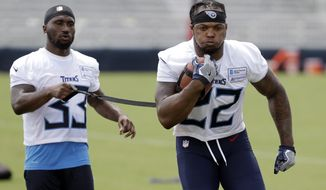 FILE - In this July 26, 2018, file photo, Tennessee Titans running back Derrick Henry (22) carries a ball tethered to a strap held by running back Dion Lewis (33) during NFL football training camp in Nashville, Tenn. Henry has a simple goal for this season as the 2015 Heisman Trophy winner chases his first starting job in the NFL: be dominant for the Titans. He won't define that by sharing any goals for yards or touchdowns, a smart move with veteran Dion Lewis also in the backfield. (AP Photo/Mark Humphrey, File)