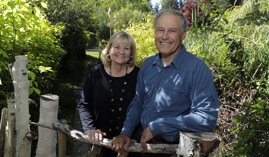 In this July 23, 2018 photo, Washington Gov. Jay Inslee, poses for a photo with his wife Trudy Inslee, at their home on Bainbridge Island, Wash. Inslee, a two-term Democratic governor and former congressman, is likely best known outside the state for his focus on climate issues and renewable energy, but lately he's getting noticed for a different role: an adversary to President Donald Trump. And while he's aware of the 2020 presidential chatter that includes his name, Inslee steers conversations on that topic to other elections. (AP Photo/Ted S. Warren)