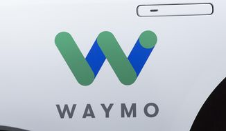 FILE - This March 27, 2018, file photo shows the Waymo logo on the of a Jaguar I-Pace vehicle, in New York. Google spinoff Waymo and Phoenix's major transit agency are partnering to test self-driving vehicles that would also boost public transportation use. Waymo announced in a blog post the start of a pilot program Tuesday, July 31, that would allow riders to hail an autonomous car to the nearest Valley Metro transit stop. (AP Photo/Mark Lennihan, File)
