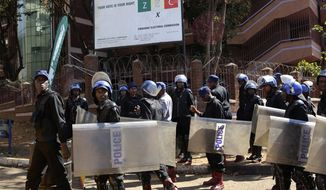 Police patrol outside the Zimbabwe Electoral Commission offices in Harare, Zimbabwe, Wednesday, Aug. 1, 2018. Zimbabwe's ruling party has won a majority of seats in Parliament, the electoral commission announced Wednesday, as the country braced for the first official results of the presidential election. (AP Photo/Tsvangirayi Mukwazhi)