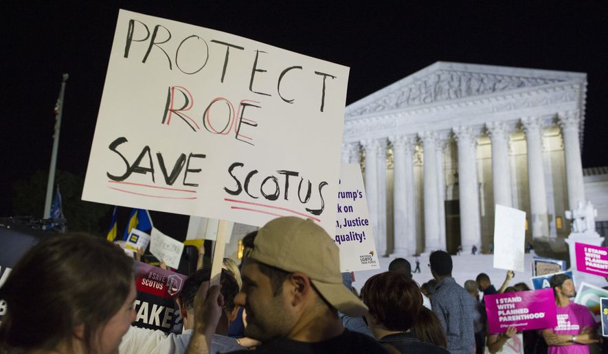 In this July 9, 2018, file photo, demonstrators holds signs as they gather in front of the Supreme Court in Washington after President Donald Trump announced Judge Brett M. Kavanaugh as his Supreme Court nominee. Worried by the prospect of a reconfigured court, abortion-rights advocates are intensifying efforts to ensure access to abortion for women who might be affected by a new wave of bans and restrictions. (AP Photo/Cliff Owen, File)