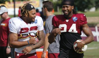 Washington Redskins running back Derrius Guice, left, and defensive back Josh Norman, right, share a laugh during the morning session at NFL football training camp in Richmond, Va., Thursday, Aug. 2, 2018. (AP Photo/Steve Helber) ** FILE **