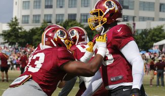 Washington Redskins defensive end Jonathan Allen, right, works with defensive end Tavaris Barnes (63) during the morning session of the Redskins NFL football training camp in Richmond, Va., Thursday, Aug. 2, 2018. (AP Photo/Steve Helber)