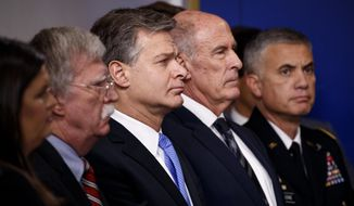 Aides to President Trump (from left) press secretary Sarah Huckabee Sanders, National Security Adviser John R. Bolton, FBI Director Christopher Wray Director of National Intelligence Dan Coats, and National Security Agency Director Gen. Paul Nakasone listen to the daily press briefing at the White House, (Associated Press/File)