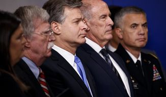 FBI Director Christopher Wray listens during the daily press briefing at the White House, Thursday, Aug. 2, 2018, in Washington. From left also listening are White House press secretary Sarah Huckabee Sanders, national security adviser John Bolton, Wray, Director of National Intelligence Dan Coats, and National Security Agency Director Gen. Paul Nakasone. (AP Photo/Evan Vucci)