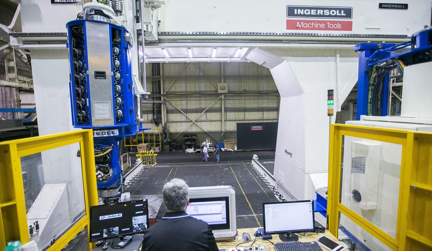 In this July 17, 2018 photo Robin Newgard, a service technician for Ingersoll Machine Tools,  operates the Mongoose the machine that will manufacture cryogenic tanks and fairings in Rockford, Ill., for Blue Origin, the rocket company founded by Amazon boss Jeff Bezos. Ingersoll has built the largest machine of its kind in the world for Bezos, who will use the engineering marvel to build rockets to carry humans to the moon and maybe even Mars. It took three years to design and manufacture the Sasquatch-sized machine, which stands 51 feet tall, 136 feet long and 43 feet wide.(Arturo Fernandez/Rockford Register Star via AP)
