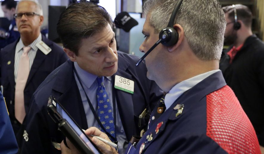 Trader Anthony Carannante, center, confers with colleague John Panin on the floor of the New York Stock Exchange, Thursday, Aug. 2, 2018. World stocks indexes are falling Thursday after the Trump administration said it will consider an even higher tax rate of 25 percent on $200 billion in imports from China, raising the stakes in the trade war between the two largest economies. (AP Photo/Richard Drew)