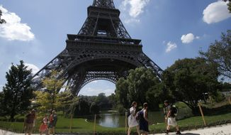 Tourists walk past the Eiffel Tower, Thursday, Aug. 2, 2018 in Paris. The visitors descending on the Eiffel Tower at the peak of the August tourist season are voicing frustration that the beloved Paris monument is closed. Since Wednesday, Eiffel Tower workers have been on strike over the new visitor access policy, which they say is responsible for inordinately long queues.(AP Photo/Michel Euler)