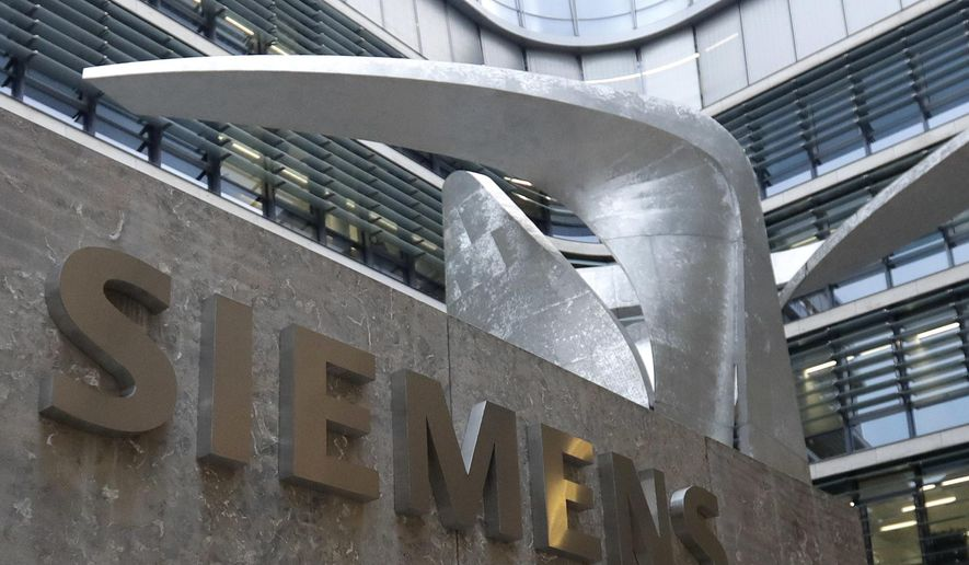 FILE - In this Thursday, Nov. 9, 2017 file photo, the logo of German industrial conglomerate Siemens in front of the headquarters in Munich, Germany. German industrial conglomerate Siemens reports its third quarter earnings on Thursday, Aug. 2, 2018. (AP Photo/Matthias Schrader, File)