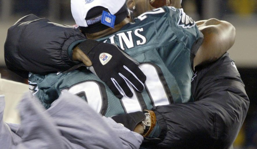 FILE - In this Jan. 23, 2005, file photo, Philadelphia Eagles wide receiver Terrell Owens hugs Eagles free safety Brian Dawkins after the Eagles 27-10 victory over the Atlanta Falcons in the NFC championship game in Philadelphia. Owens is skipping his induction ceremony into the Pro Football Hall of Fame in Canton, Ohio on Saturday, Aug. 4, 2018, and instead giving his acceptance speech at the University of Tennessee at Chattanooga. (AP Photo/Miles Kennedy)