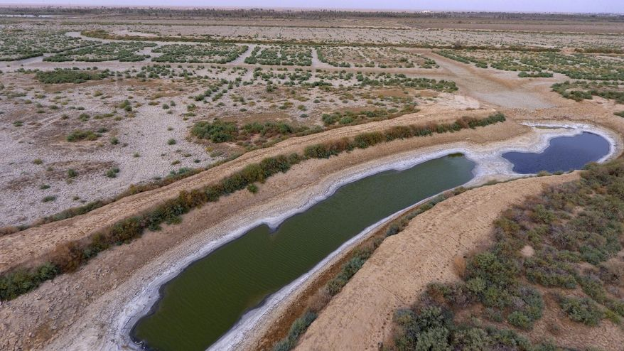 """This canal southeast of Baghdad is dry and filled with salt. Iraq, historically known as """"The Land Between The Two Rivers,"""" is struggling with the scarcity of water because of dams in Turkey and Iran, a lack of rainfall and aging hydrological infrastructure. The decreased water levels have dramatically affected agriculture and animal resources. (Associated Press/File)"""