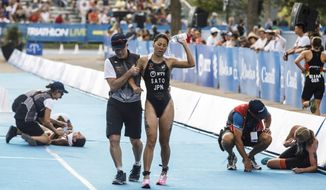 Japan's Yuka Sato is helped off the course after finishing the mixed relay at the ITU World Triathlon Series in Edmonton, Alberta, Saturday July 28, 2018. (Jason Franson/The Canadian Press via AP)