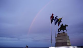 A rainbow crosses the sky over a statue of Simon Bolivar on the shore of Managua Lake at sunset in Managua, Nicaragua, Wednesday, Aug. 1, 2018. (AP Photo/Arnulfo Franco)