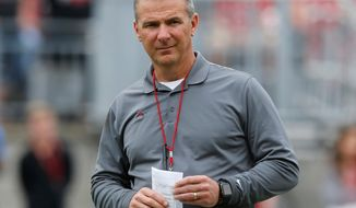 FILE - In this April 14, 2018, file photo, Ohio Setate coach Urban Meyer watches the NCAA college football team's spring game in Columbus, Ohio. Ohio State has placed Meyer on paid administrative leave while it investigates claims that his wife knew about allegations of abuse against an assistant coach years before he was fired last week. (AP Photo/Jay LaPrete, File)