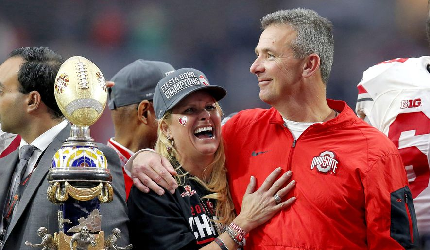 In this Jan. 1, 2016, file photo, Ohio State head coach Urban Meyer hugs his wife, Shelley, after their 44-28 win over Notre Dame in the Fiesta Bowl NCAA college football game, in Glendale, Ariz. Ohio State placed Meyer on paid administrative leave Wednesday, Aug. 1, 2018, while it investigates claims that his wife knew about allegations of abuse against former Buckeyes assistant Zach Smith, who was fired last week. (AP Photo/Rick Scuteri, File)
