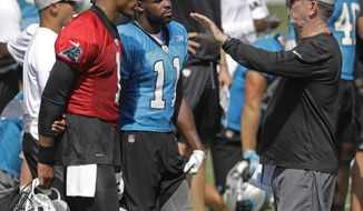 FILE - In this July 27, 2018, file photo, Carolina Panthers offensive coordinator Norv Turner, right, talks with Cam Newton, left, and Torrey Smith, back, during an NFL football practice at the team's training camp in Spartanburg, S.C. Panthers new offensive coordinator Norv Turner is expected to address his decision to come out of retirement to coach at age 66, his relationship with quarterback Cam Newton and thoughts on the Panthers offense heading into the season. (AP Photo/Chuck Burton, File)