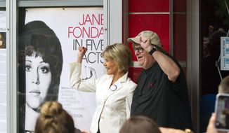 "Actress Jane Fonda, left, and director Michael Moore pose for photos outside the State Theatre before the ""One-on-One With Jane Fonda,"" panel during the Traverse City Film Festival Wednesday, Aug. 1, 2018, in Traverse City, Mich. Fonda is receiving the festival's Lifetime Achievement Award.  (Jan-Michael Stump/Traverse City Record-Eagle via AP)"