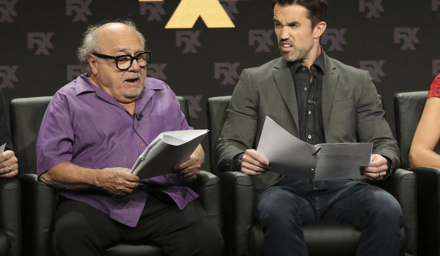 """Danny DeVito, left, and Rob McElhenney, creator/writer/executive producer/actor, participate in a table read during a panel for """"It's Always Sunny in Philadelphia"""" during the FX Television Critics Association Summer Press Tour at The Beverly Hilton hotel on Friday, Aug. 3, 2018, in Beverly Hills, Calif. (Photo by Willy Sanjuan/Invision/AP)"""