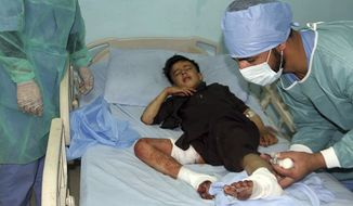Doctors assist a wounded young man in a hospital after a deadly attack on a Shiite mosque in Gardez, the capital of Paktia, Afghanistan, Friday, Aug. 3, 2018.  Two suicide bombers attacked the Shiite mosque in eastern Afghanistan during Friday prayers, killing several people and wounding anothers, officials said. (AP Photo) ** FILE **