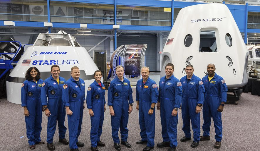 This undated photo made available by NASA on Friday, Aug. 3, 2018 shows, from left, Sunita Williams, Josh Cassada, Eric Boe, Nicole Mann, Christopher Ferguson, Douglas Hurley, Robert Behnken, Michael Hopkins and Victor Glover standing in front of Boeing's CST-100 Starliner and SpaceX's Crew Dragon capsules at the Kennedy Space Center in Florida. On Friday, the space agency announced the astronauts who will ride the first commercial capsules into orbit next year and bring human launches back to the U.S. (NASA via AP)