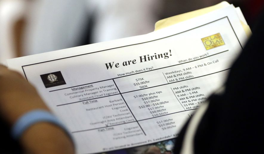 FILE In this June 21, 2018, file photo, a job applicant looks at job listings for the Riverside Hotel at a job fair hosted by Job News South Florida, in Sunrise, Fla. (AP Photo/Lynne Sladky) ** FILE **