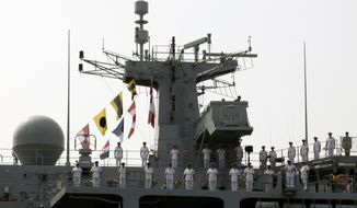 Sailors of British Royal Navy's HMS Albion amphibious assault ship man the rails upon arrival at a dock in Tokyo Friday, Aug. 3, 2018. The British warship has docked in Tokyo as Britain seeks to expand its military presence in the Asia-Pacific region. (AP Photo/Ken Moritsugu)