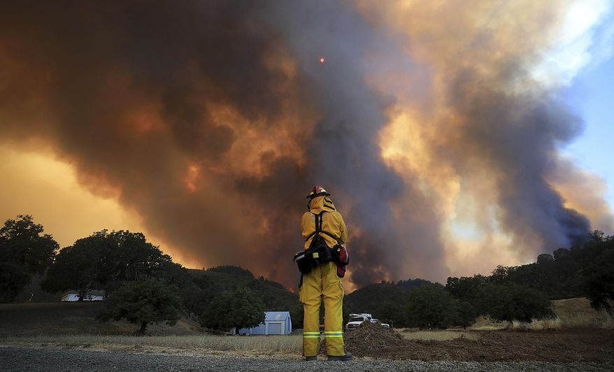 A tower of smoke pours from Cow Mountain as Burney, California firefighter Bob May keeps a watch on surrounding vegetation for spot fires during a wildfire off Scotts Valley Road, Thursday, Aug. 2, 2018, near Lakeport, Calif.  (Kent Porter /The Press Democrat via AP)