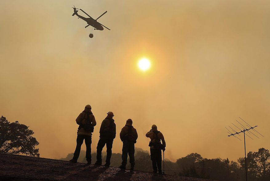 Firefighters stand watch on a roof as a wildfire sweeps through the area near Lakeport, Calif., Thursday, August 2, 2018. (Kent Porter /The Press Democrat via AP)